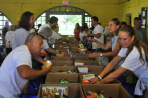 Volunteers at last year's event pack donated goods into bags and boxes to be distributed in the community. 14850 Photo by Mark H. Anbinder.