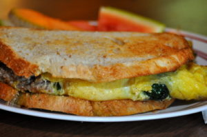 A sausage, spinach, and gruyere breakfast sandwich on French peasant bread.