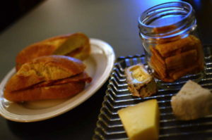 "A sandwich of Piggery capicola on Ithaca Bakery baguette, and a ""Chaseholm"" cheese plate with cheese crisps."