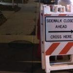 "Sign says ""Sidewalk closed ahead. Cross here."""