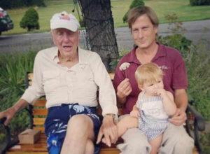 Un homme plus âgé, un homme plus jeune et un enfant en bas âge sont assis sur un banc